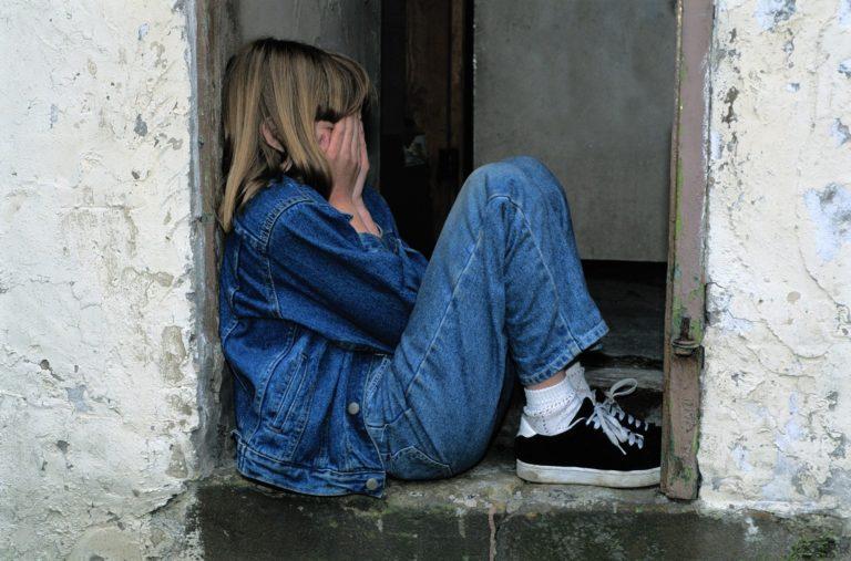 Kind sitzt im Türeingang eines alten Hauses